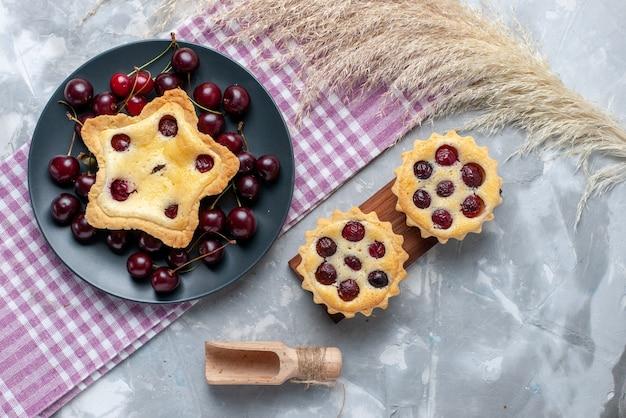 Vista de cima do bolo em forma de estrela junto com bolos de cereja e cerejas frescas na torta de mesa clara