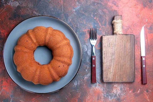 Vista de cima do bolo - o garfo e a faca da tábua ao lado do bolo apetitoso no prato