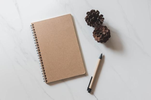 Vista de cima do caderno com cone de pinho e caneta no fundo de mesa de mármore branco