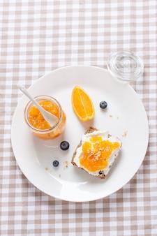 Vista de cima do café da manhã com pão e laranja marmelada