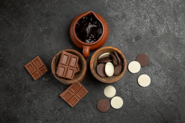 Vista de cima do chocolate na mesa sobre a superfície escura chocolate e calda de chocolate nas tigelas
