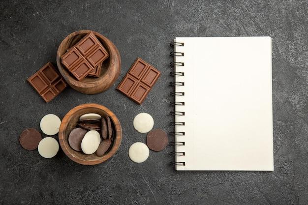 Vista de cima do chocolate na mesa, taças de chocolate marrons ao lado do caderno branco no fundo escuro