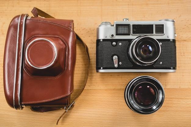 Vista de cima do conjunto de fotografia retrô de câmera, caixa e lente em fundo de madeira