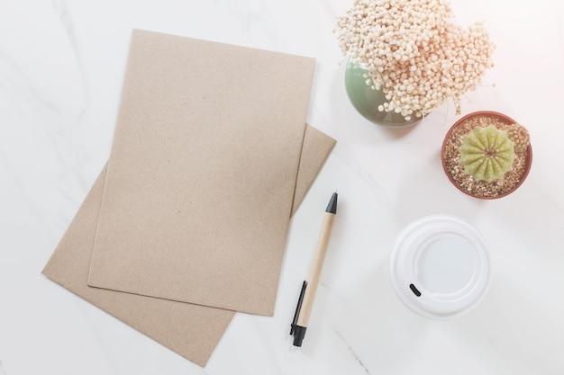 Vista de cima do envelope, caneta, cacto, copo de café e flor no fundo de mesa de mármore branco