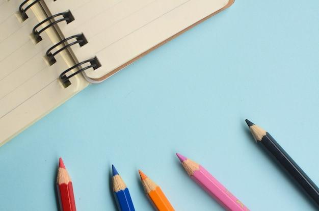 Vista de cima do espaço vazio com lápis de cor e cadernos em um fundo azul