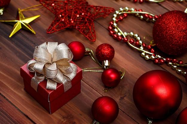 Vista de cima do festival de natal e itens decorativos de feliz ano novo. bolas vermelhas brilhantes decoração prata lâmpada talão cadeia caixa de presente estrela dourada brilhante com fita colocada na velha mesa de madeira escura.
