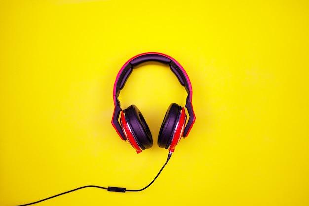 Vista de cima do fone de ouvido vermelho sobre fundo de papel amarelo claro. plano de fundo mínimo. de cima para baixo.