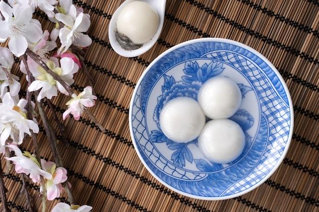 Vista de cima do grande tangyuan yuanxiao (bolinhas de massa de arroz glutinoso) para a comida do festival do ano novo lunar, as palavras na moeda dourada significam o nome da dinastia que ela fez.
