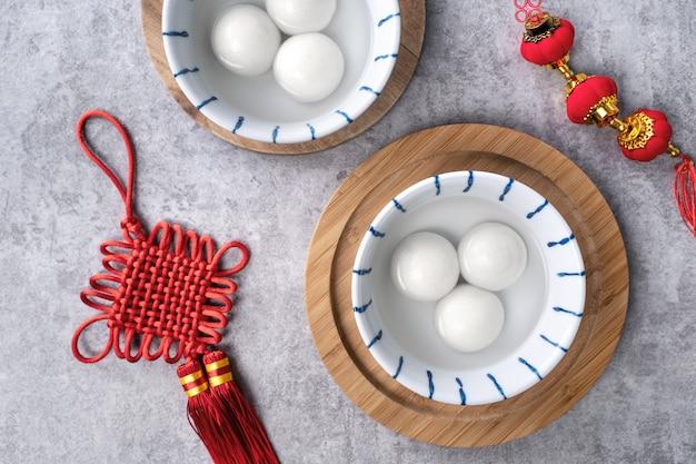 Vista de cima do grande tangyuan yuanxiao (bolinhos de arroz glutinosos) para a comida chinesa do festival do ano novo lunar, as palavras na moeda de ouro significam o nome da dinastia criado.