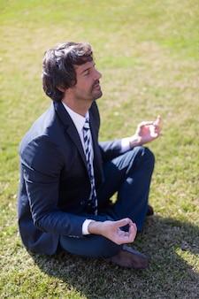 Vista de cima do homem de negócios praticando exercícios de ioga