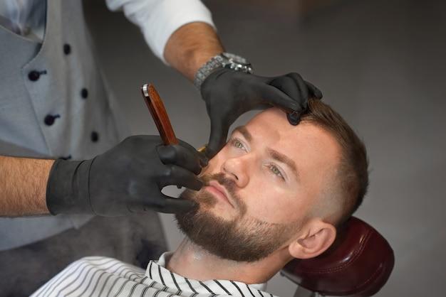 Vista de cima do homem na cadeira enquanto barbeiro barbear barba