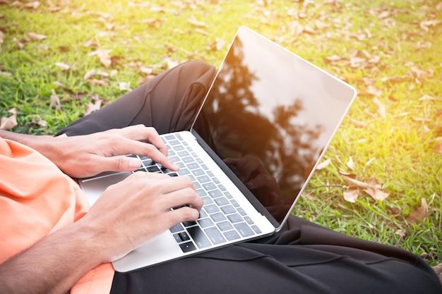 Vista de cima do jovem sentado no parque na grama verde com laptop