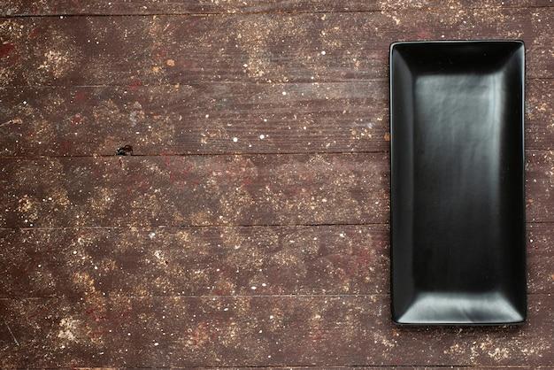 Vista de cima do molde de bolo preto longo do marrom rústico, bolo de comida, assar mesa doce, madeira