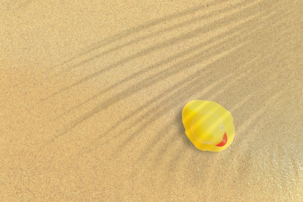 Vista de cima do pato de borracha amarelo na praia de areia. fundo do conceito de férias.
