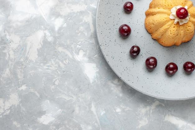 Vista de cima do pequeno bolo com cerejas dentro do prato na luz cinza, bolo biscoito açúcar doce assar frutas