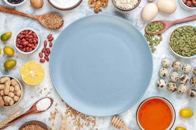 Vista de cima do prato azul com ovos de geleia de farinha e diferentes nozes em frutas brancas, nozes, açúcar foto, torta de massa doce colorida