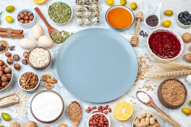 Vista de cima do prato azul com ovos de geleia de farinha e nozes diferentes em uma massa branca bolo de frutas foto de açúcar torta de noz