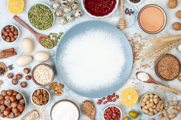 Vista de cima do prato azul com ovos, farinha, geléia e diferentes nozes em um bolo claro, cor de açúcar, massa, frutas, doce, noz, torta