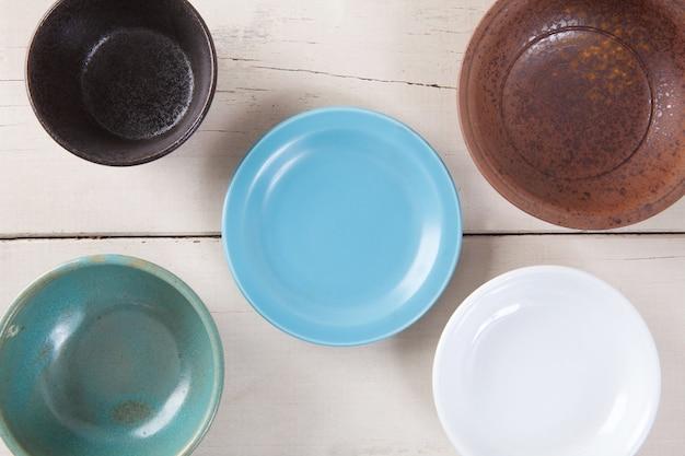 Vista de cima do prato colorido vazio colocado na mesa de madeira branca.