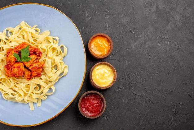 Vista de cima do prato com molhos de carne e molho com macarrão no prato ao lado dos três tipos de molhos na mesa escura