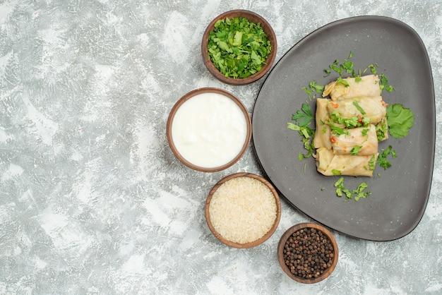 Vista de cima do prato com prato de ervas de repolho recheado ao lado da tigela com arroz de creme azedo de ervas e pimenta do reino do lado direito da mesa