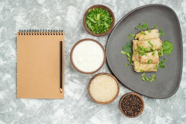 Vista de cima do prato com prato de ervas de repolho recheado ao lado do caderno de creme com lápis e tigelas de arroz de creme azedo de ervas e pimenta preta na mesa