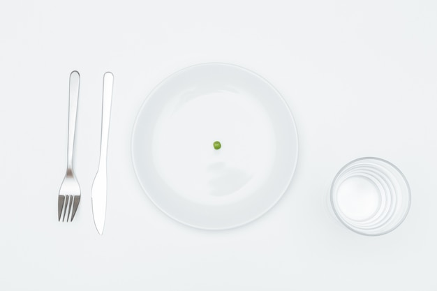 Vista de cima do prato com uma ervilha verde, copo d'água? garfo e faca