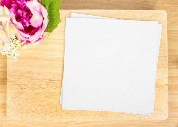 Vista de cima do prato de madeira em branco com papel branco e vaso de flores no topo da mesa