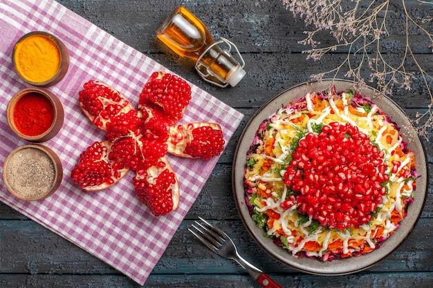 Vista de cima do prato e prato de toalha de mesa de batata-cenoura e romã ao lado da garrafa de galhos de árvore de garfo de óleo e especiarias de romã empilhadas em toalha de mesa quadriculada rosa-branca