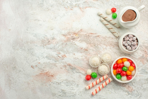 Vista de cima doces coloridos com biscoitos no fundo branco claro cor arco-íris biscoito chá bolo