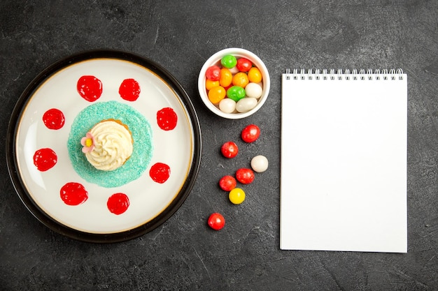 Vista de cima doces na mesa queque apetitoso ao lado da tigela de doces e caderno branco na mesa preta