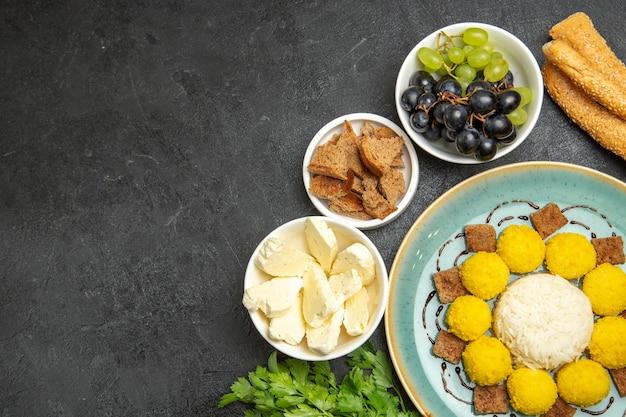 Vista de cima, doces saborosos doces com queijo branco e uvas na superfície escura frutas doces chá doce guloseima doce
