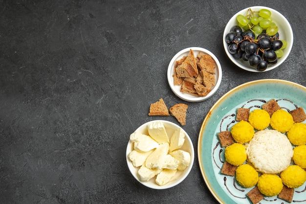Vista de cima doces saborosos doces com queijo branco e uvas na superfície escura frutas doces chá doce guloseima doce