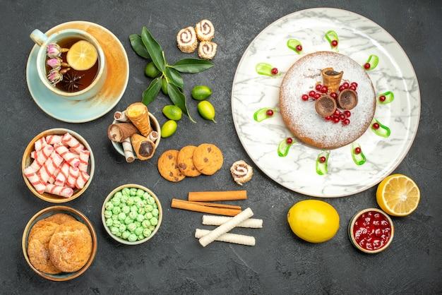 Vista de cima doces uma xícara de chá de ervas um bolo com frutas, biscoitos, waffles, doces, geléia, limão