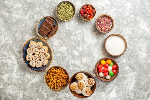 Vista de cima dos doces coloridos com rebuçados rolinhos doces na mesa branca