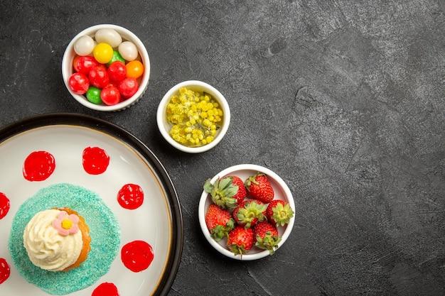 Vista de cima dos doces no prato da mesa com molhos coloridos ao lado das tigelas de ervas de morangos e doces na mesa
