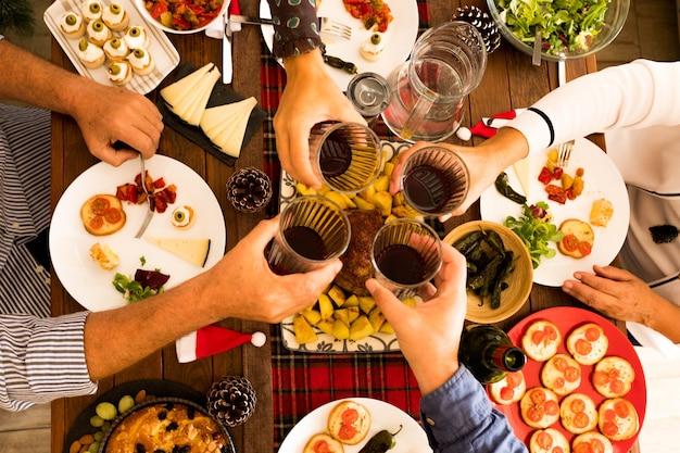 Vista de cima e de cima em uma grande mesa cheia de comida, como frango e muito mais no jantar ou almoço - grupo de mãos tilintando com garrafas de vinho