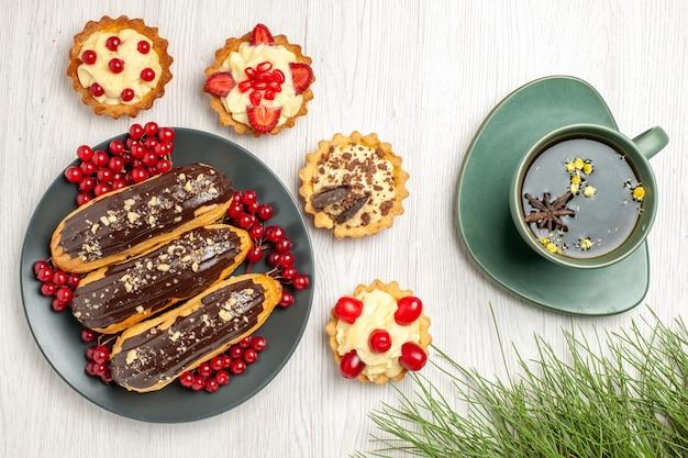 Vista de cima, éclairs de chocolate e groselhas no prato cinza cercado com tortas, uma xícara de chá e folhas de pinheiro na mesa de madeira branca