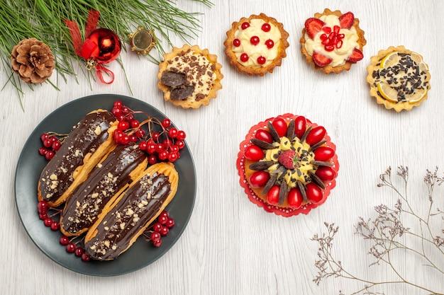 Vista de cima, éclairs de chocolate e groselhas no prato cinza tortas de bolo de frutas vermelhas e folhas de pinheiro com brinquedos de natal na mesa de madeira branca