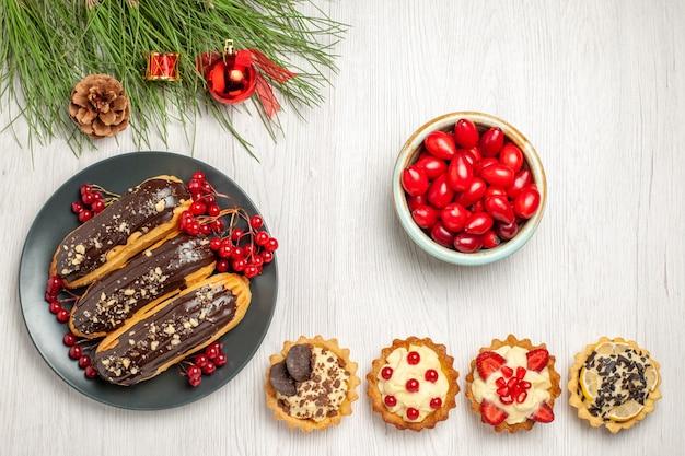 Vista de cima éclairs de chocolate e groselhas no prato cinza uma tigela de tortas de cornel e folhas de pinheiro com brinquedos de natal no chão de madeira branco com espaço de cópia