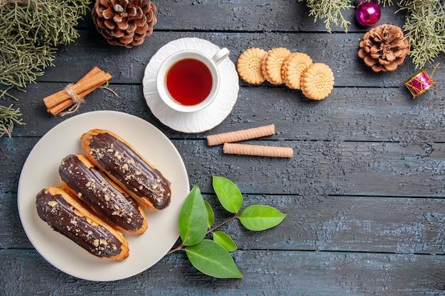 Vista de cima éclairs de chocolate em cones de placa oval branca, brinquedos de natal, árvore de abeto folhas de canela e biscoitos diferentes em chão de madeira escura com espaços de cópia