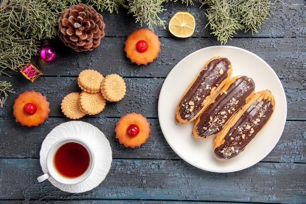 Vista de cima éclairs de chocolate em placa oval branca ramos de árvore de abeto brinquedos de natal fatia de limão uma xícara de biscoitos de chá e cupcakes em chão de madeira escura