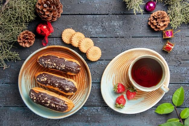 Vista de cima éclairs de chocolate em um prato oval, uma xícara de chá e morangos no pires, pinhas, brinquedos de natal, abeto deixa biscoitos no chão de madeira escura