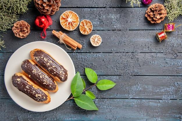 Vista de cima éclairs de chocolate em uma placa oval branca cones brinquedos de natal árvore de abeto folhas de laranja seca de canela em chão de madeira escura com espaço de cópia