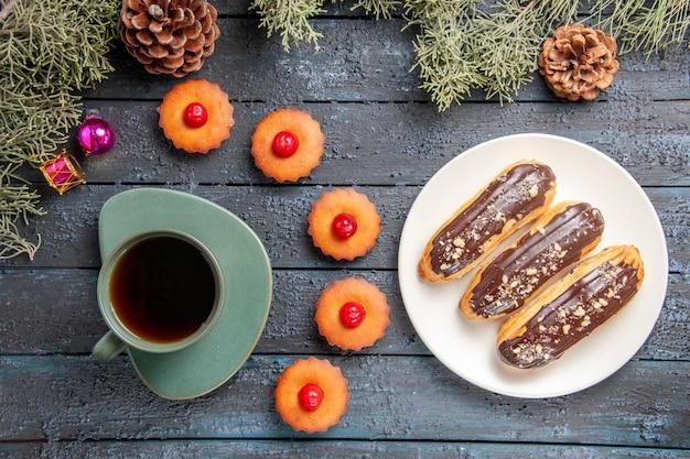 Vista de cima éclairs de chocolate em uma placa oval branca, galhos de pinheiro e cones, biscoitos de brinquedos de natal e uma xícara de chá na mesa de madeira escura