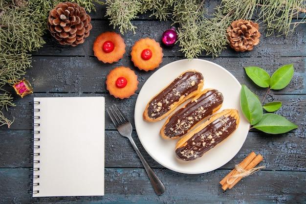 Vista de cima éclairs de chocolate em uma placa oval branca, galhos e cones de árvore do abeto, brinquedos de natal, garfo canela, xícara de chá e caderno, mesa de madeira escura