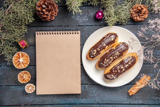 Vista de cima éclairs de chocolate em uma placa oval branca galhos e cones de pinheiro-alvarinho brinquedos de natal galho de flores secas laranjas secas canela e um caderno na mesa de madeira escura