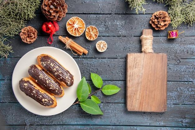 Vista de cima éclairs de chocolate em uma placa oval cones brinquedos de natal árvore do abeto folhas de laranjas secas de canela e tábua de cortar no chão de madeira escura