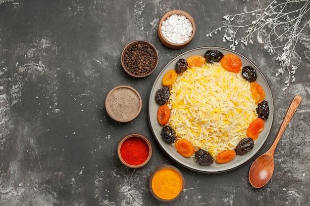 Vista de cima, em close-up, arroz, arroz com frutas secas no prato, cinco tigelas de especiarias na mesa