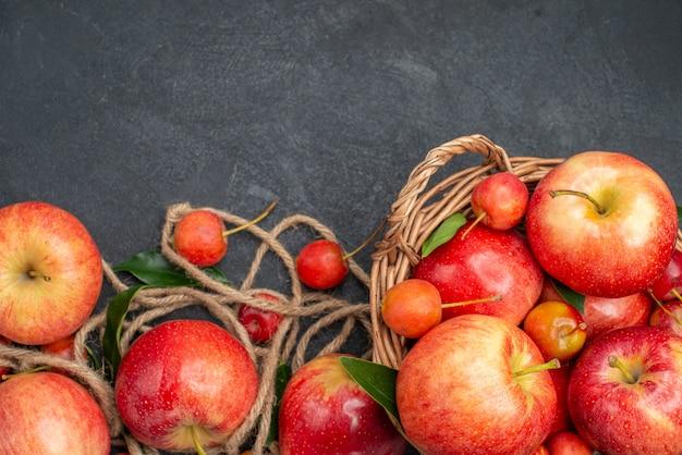 Vista de cima em close-up, as maçãs amarram as apetitosas maçãs e cerejas na cesta na mesa escura